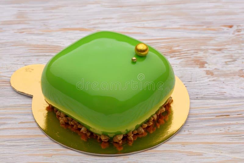 Ультрамодный зеленый торт мусса при украшенная полива зеркала Деревянная предпосылка стоковое фото rf