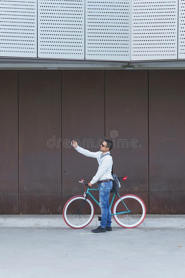 Ультрамодный человек принимая selfie с его фиксированным велосипедом стоковые изображения