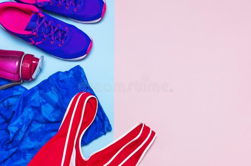 Ультрафиолетов женские тапки, гетры и бутылка с водой пинка верхние голубые спортивные на пастельном розовом взгляде сверху предп стоковое фото rf