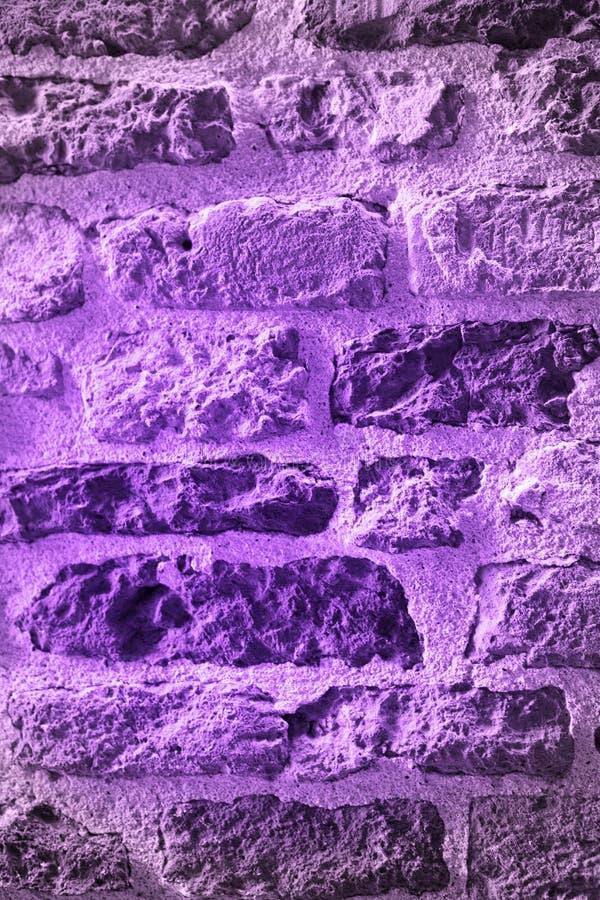Ультрафиолетов ультрамодная концепция цвета Кирпичная стена покрашена на ультрафиолетовом луче стоковое фото rf