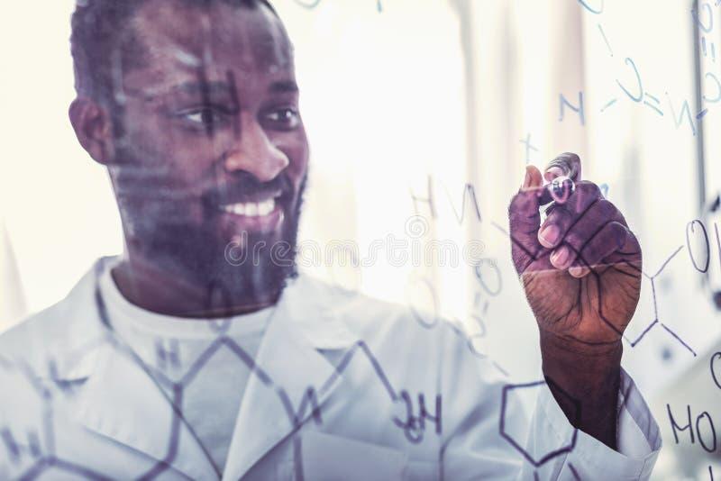 Умелое молодое химическое ассистентское положение около стеклянной доски стоковая фотография