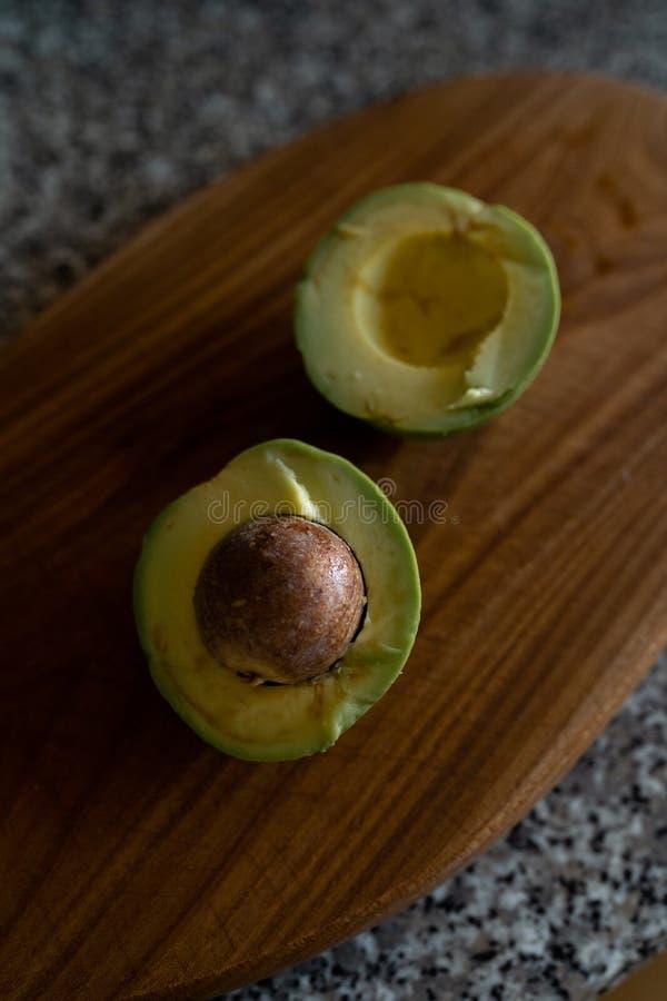 Уменьшанные вдвое авокадоы - взгляд сверху свежих фруктов получая отрезок на доске стоковое изображение