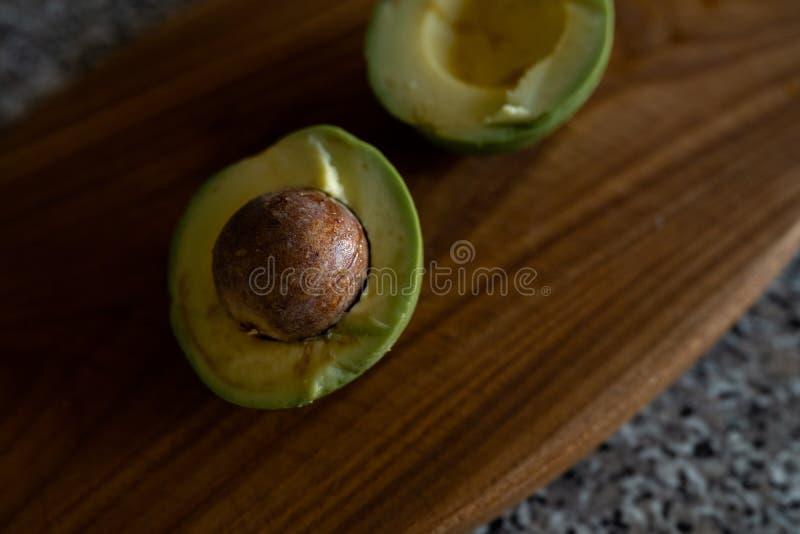 Уменьшанные вдвое авокадоы - взгляд сверху свежих фруктов получая отрезок на доске стоковая фотография