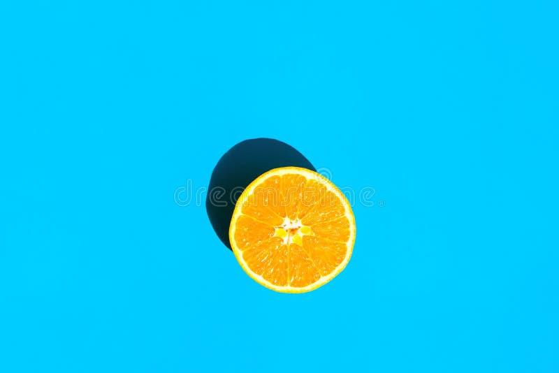 Уменьшанный вдвое зрелый сочный апельсин на голубой предпосылке Тень яркого жесткого солнечного света глубокая Живые неоновые цве стоковые изображения