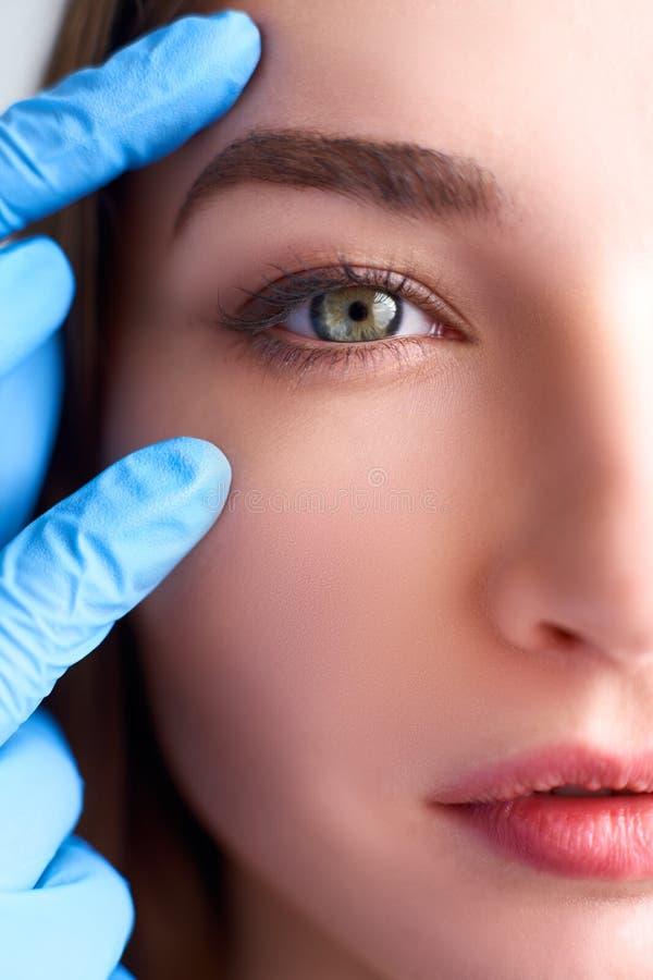 Уменьшение верхнего века, концепция пластической хирургии удаления крышки двойного глаза Руки доктора Beautician в касаться перча стоковое изображение