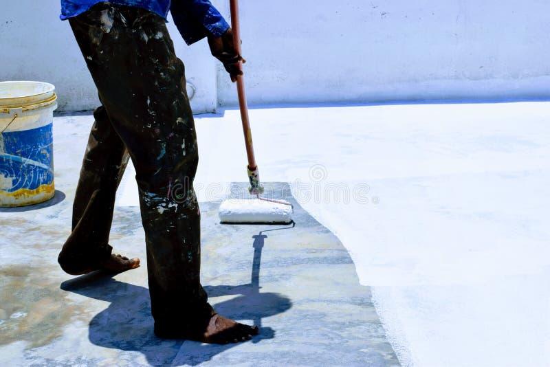 Уменьшите жару в доме путем красить краску пальто крыши белую стоковое изображение rf