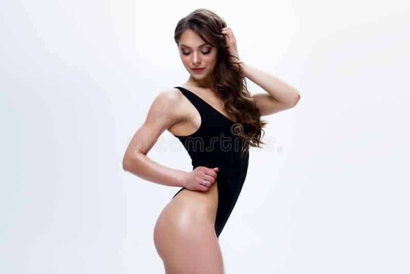 Уменьшите женскую модель в черном bodysuit на белой предпосылке стоковая фотография