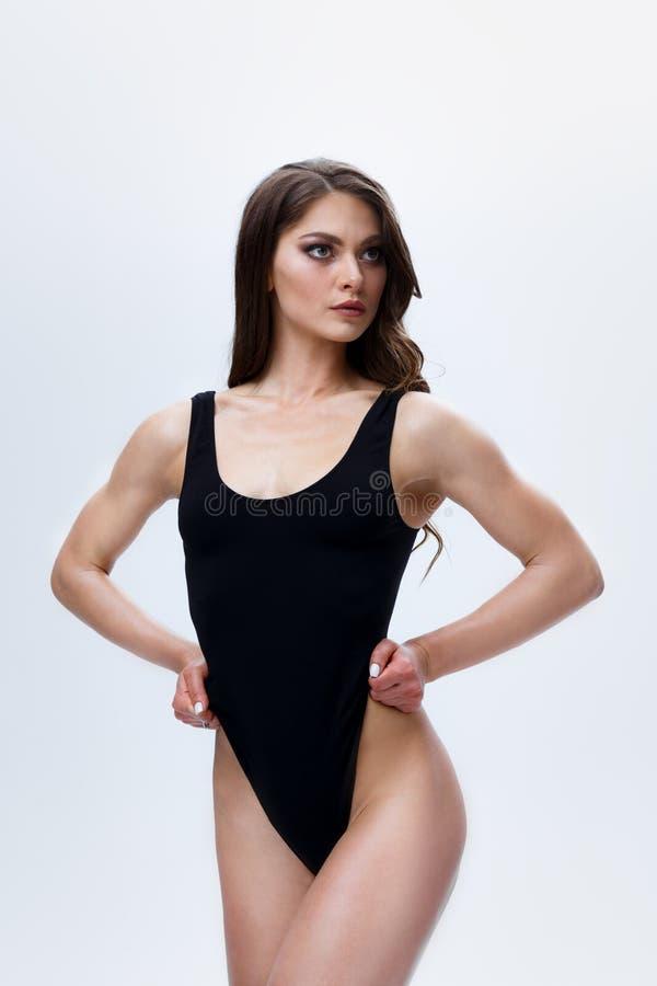 Уменьшите женскую модель в черном bodysuit на белой предпосылке стоковое фото rf