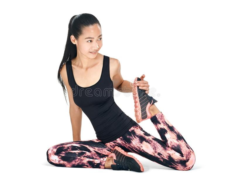 Уменьшите протягивать подходящей молодой восточной женщины сидя на ее ноге стоковое изображение