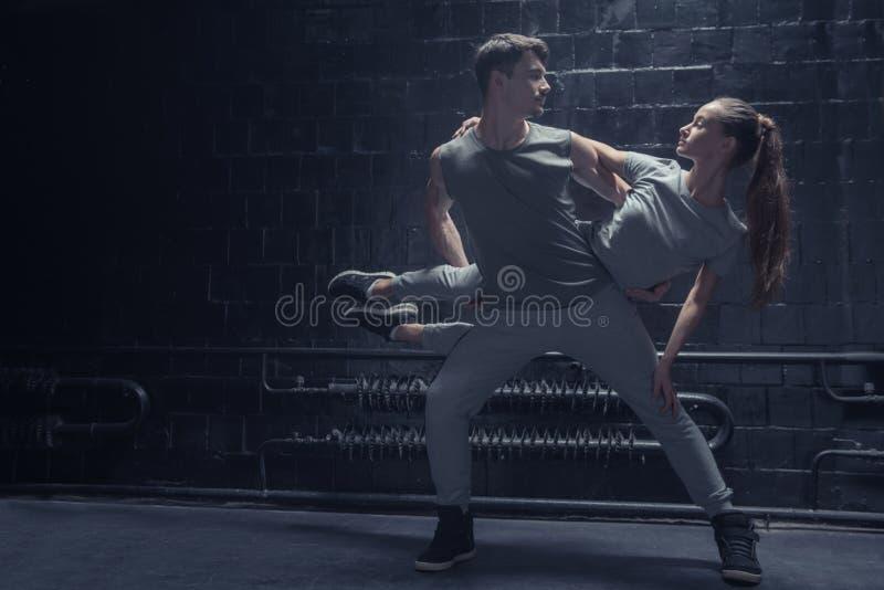 Умелые танцоры выполняя в темноте осветили комнату стоковые фотографии rf