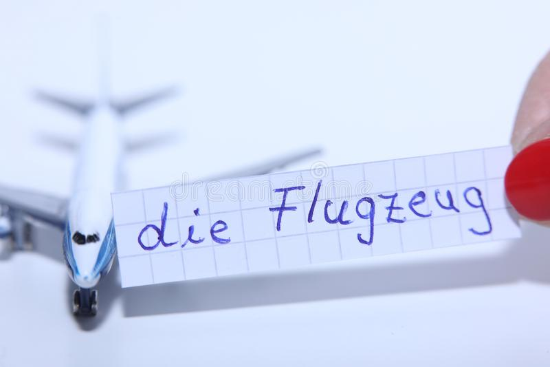 Умирает слово Flugzeug в немце для самолета в английском стоковые фото