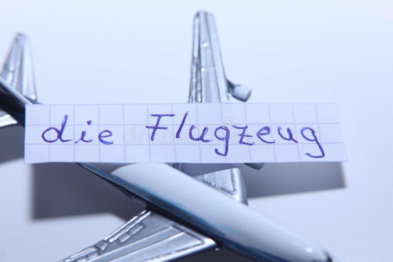 Умирает слово Flugzeug в немце для самолета в английском стоковая фотография