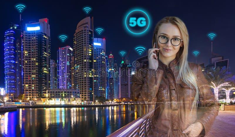 Умная бизнес-леди с современным городом в предпосылке вечером используя беспроводную связь скорости 5G, который нужно вызвать со  стоковое изображение