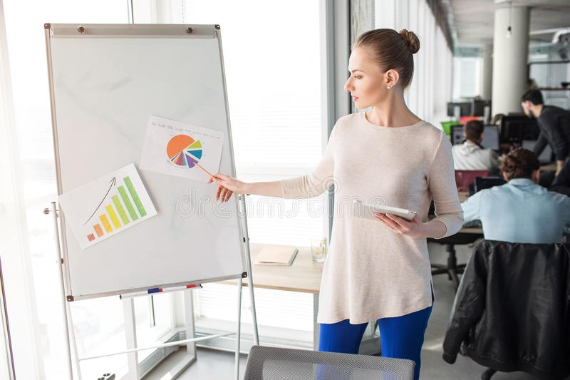 Умная и славная женщина стоящее близко flipchart и диаграммы представлять на ей Она стоит около большого и яркого окна стоковое изображение rf