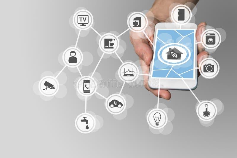 Умная домашняя концепция при рука держа современный умный телефон для того чтобы контролировать бытовые устройства стоковая фотография rf