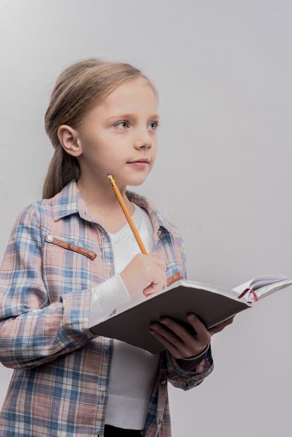 Умная симпатичная белокур-с волосами школьница делая ее домашнюю работу стоковая фотография rf