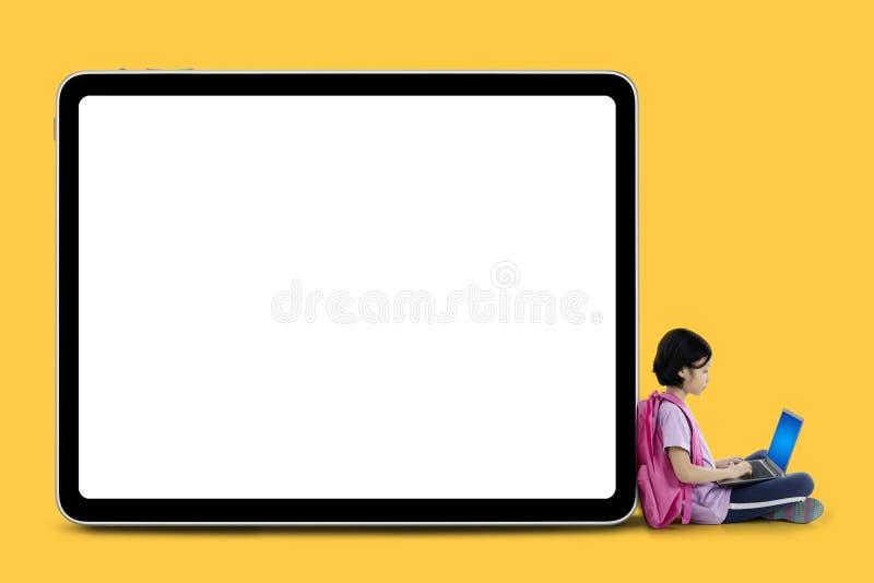 Умная школьница с компьтер-книжкой около whiteboard стоковая фотография