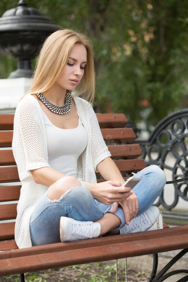 Умное чтение профессиональной женщины используя телефон стоковое фото rf