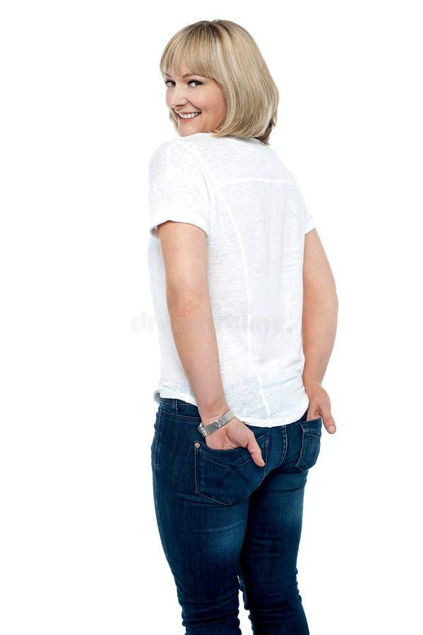 Умно одетая женщина с руками в заднем карманн джинсыов стоковое фото rf