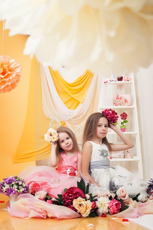 Умные девушки представляя с цветками в винтажной студии стоковые фотографии rf