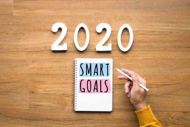 2020, умные концепции цели с блокнотом и мужская рука на деревянной предпосылке Проблема дела Идеи воодушевленности стоковое фото