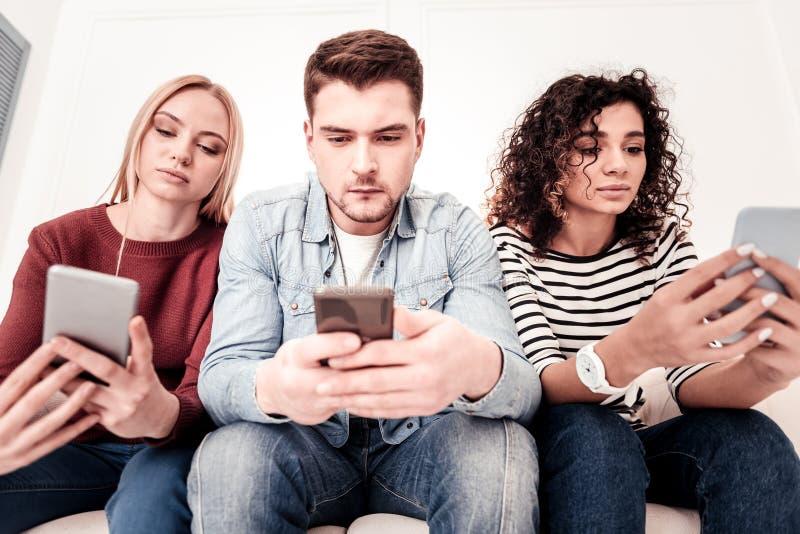 Умные молодые люди используя их смартфоны стоковые изображения rf