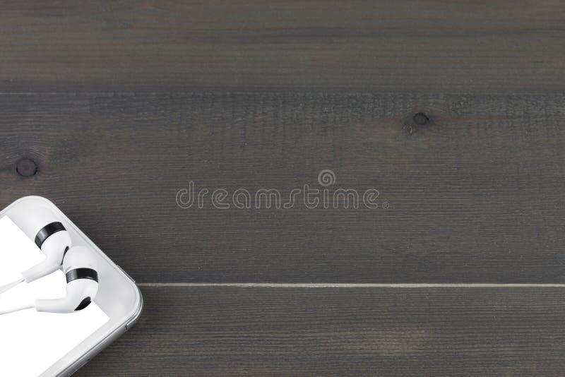 Умные телефон и наушник на деревянной предпосылке стоковая фотография