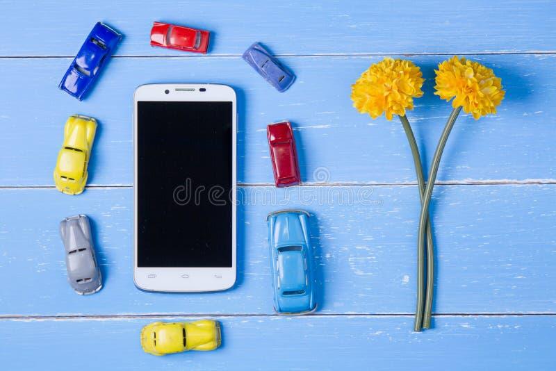 умные телефон, игрушки автомобиль и цветки пластмассы на голубом деревянном bac стоковое фото