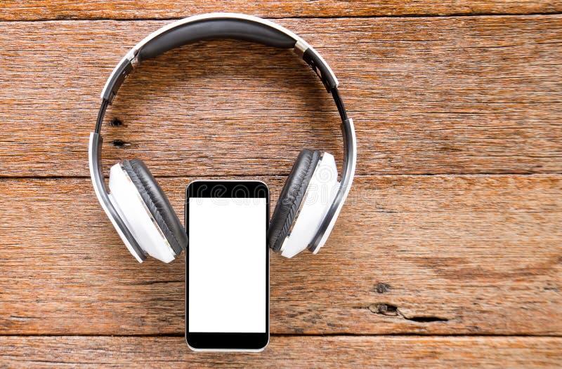 Умные телефон и наушник на деревянном поле стоковая фотография
