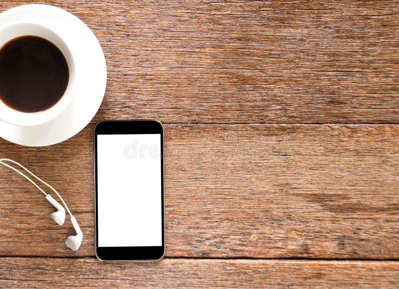 Умные телефон и наушник с кофе на деревянном поле стоковое изображение