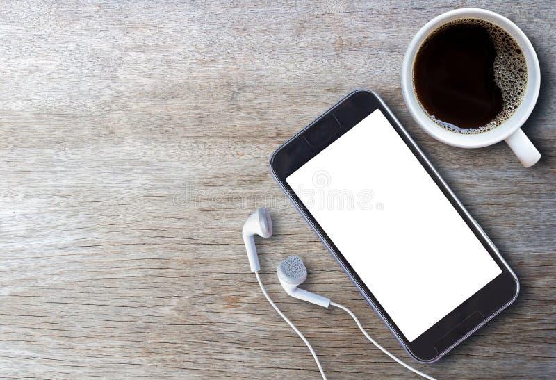 Умные телефон и наушник с чашкой кофе стоковые изображения