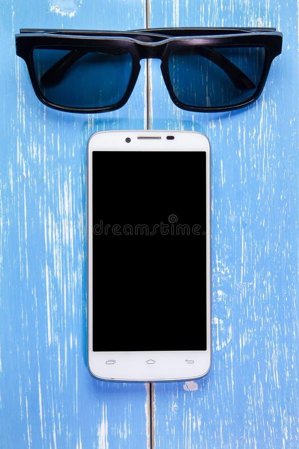 Умные телефон и солнечные очки на голубой деревянной предпосылке стоковые фотографии rf
