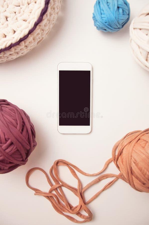 Умные телефон и шарики пряжи футболки стоковая фотография