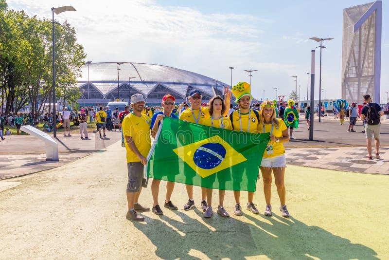 умные футбольные болельщики с национальным флагом в Бразилии против ф стоковое изображение rf