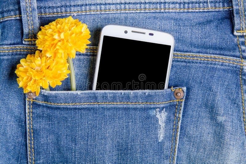 Умные цветки телефона и пластмассы в задних карманных джинсах Джинсы b стоковая фотография