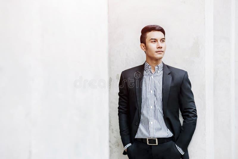 Умный азиатский бизнесмен в вскользь костюме, смотря вперед для Succ стоковые фото