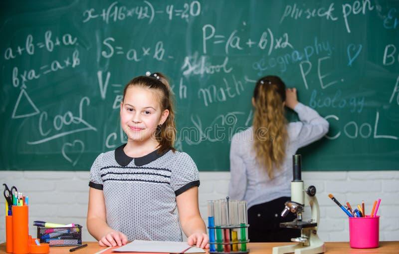 Умный и уверенный Маленькие девочки в лаборатории школы Образование химии Урок биологии эксперименты по науки в химии стоковые фото