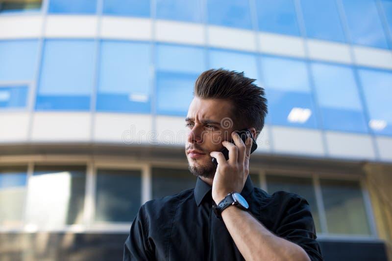 Умный менеджер человека говоря через мобильный телефон пока стоящ бизнес-центр outdoors стоковое изображение rf