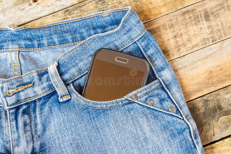 Умный телефон в карманных голубых джинсах стоковое изображение rf