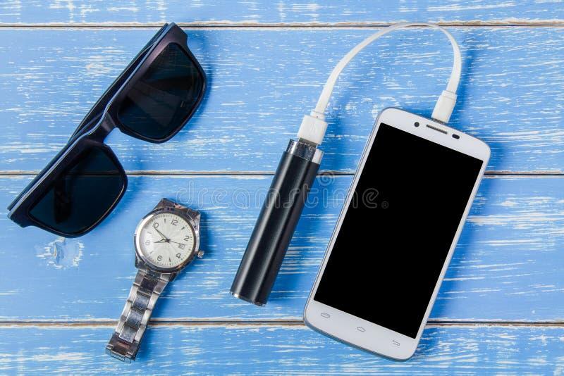 Умный телефон, солнечные очки, портативная батарея и вахта на голубой древесине стоковые фотографии rf