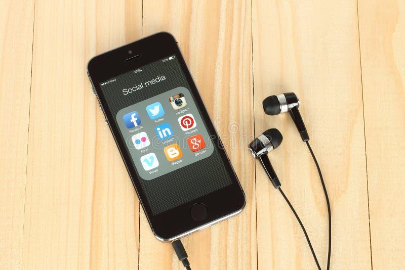 Умный телефон с социальными логотипами средств массовой информации на своих экране и наушниках стоковые изображения