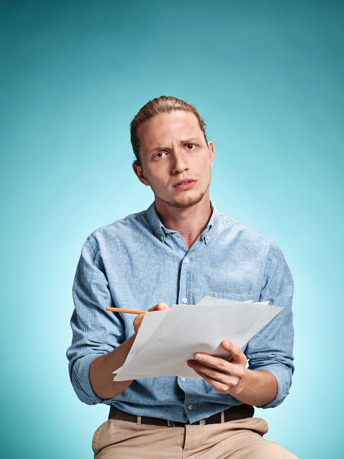 Умный унылый студент с листами бумаги стоковое фото rf
