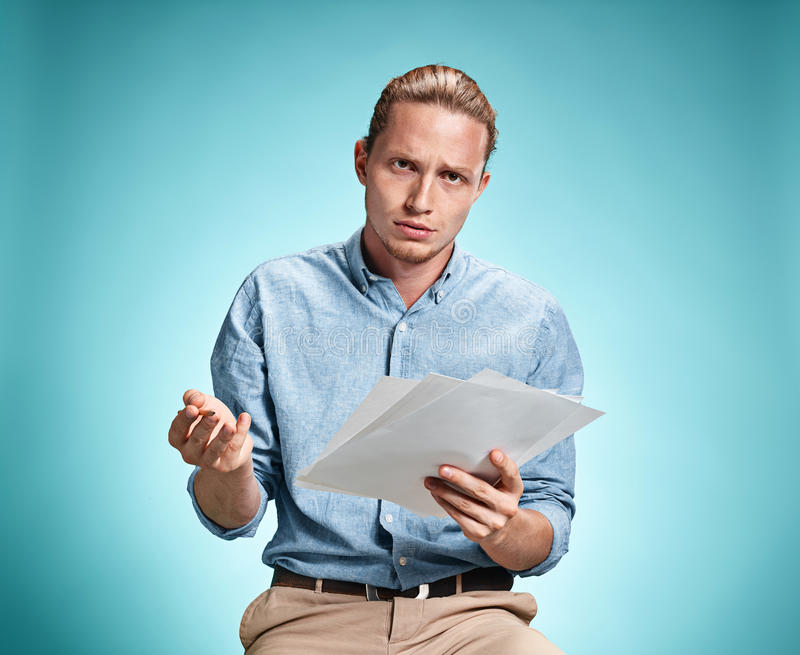 Умный унылый студент с листами бумаги стоковое изображение