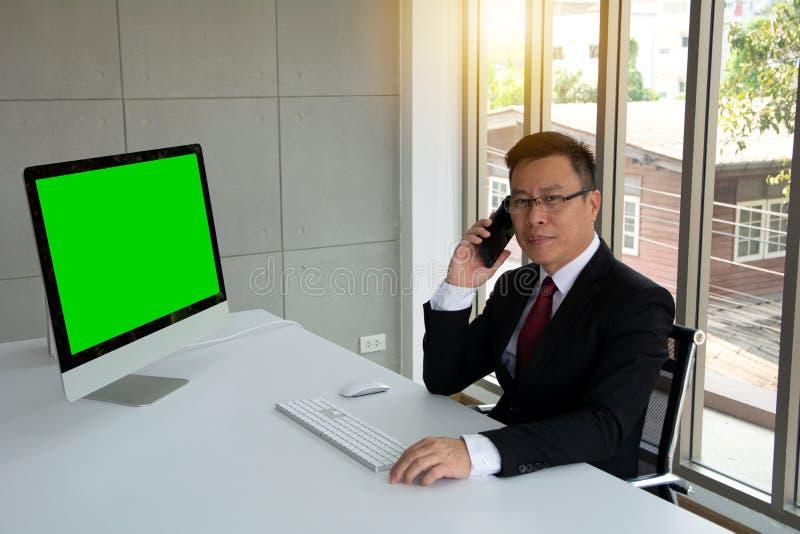 Умный усмехаясь бизнесмен говоря с данными по мобильного телефона осматривая на рабочем столе стоковое фото rf