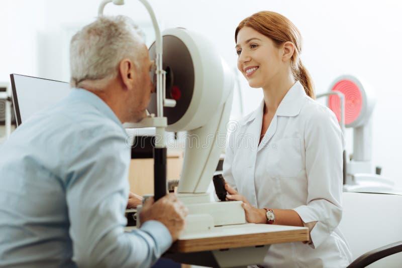 Умоляющий офтальмолог усмехаясь пока работающ стоковая фотография rf