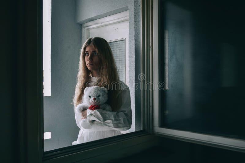 Умственно - больная девушка с смирительной рубашкой в психиатрическом стоковые фотографии rf