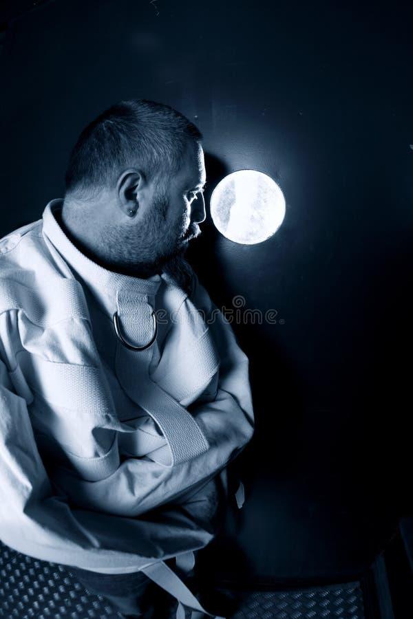 Умственно - больной человек смотря вне его клетку стоковое изображение rf