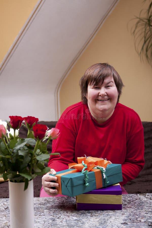Умственно - неработающая женщина держа много подарков стоковое изображение