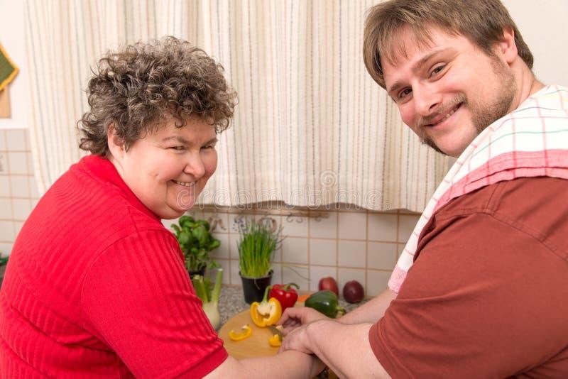 Умственно - неработающая женщина и молодой человек варя совместно стоковое фото rf