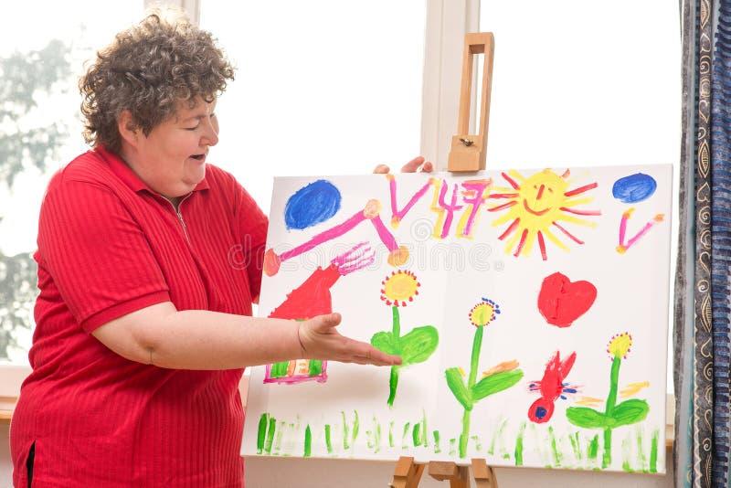 Умственно - неработающая женщина показывая ее картину стоковые изображения rf